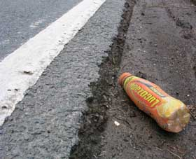 An empty bottle of lucozade alongside the B5105 road